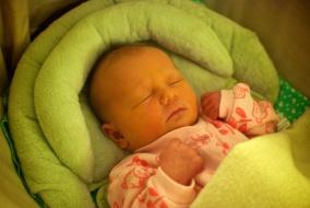 Baby Eva lying in her moses basket